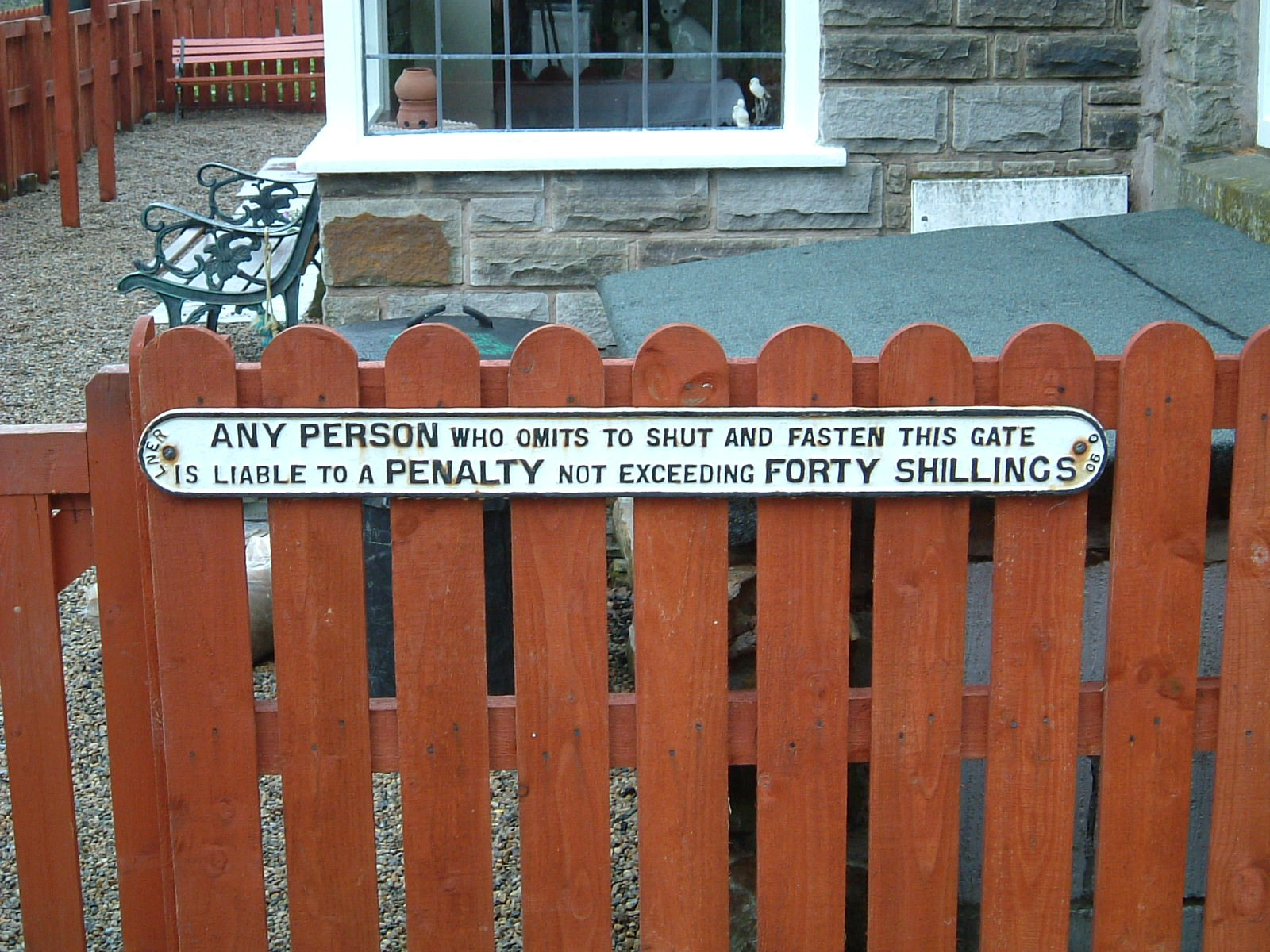 A sign on a gate saying the charge for not shutting it is 40 shillings