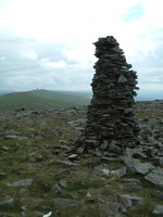 A cairn on the flanks of Cross Fell with Great Dun Fell's radar station in the background