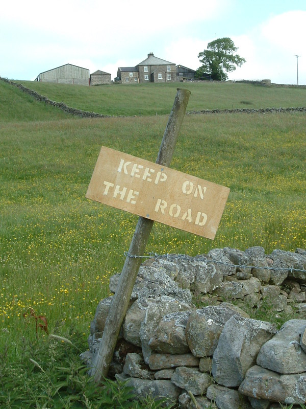 A sign saying 'Keep on the Road'