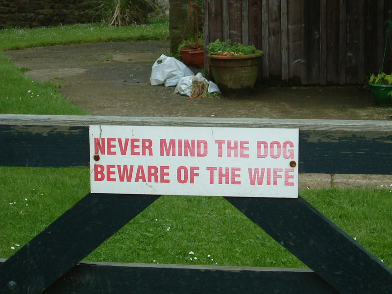 A sign saying 'Never Mind the Dog, Beware of the Wife'