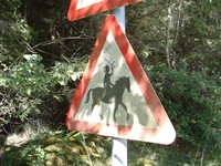 A road sign warning of people on horses, on which someone has added a sword in the hand of the rider