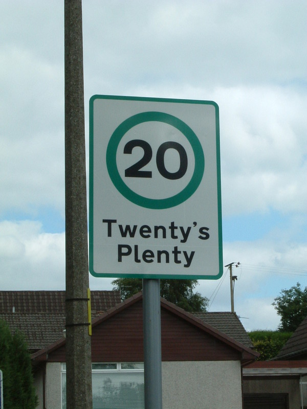 A speed limit sign saying 'Twenty's Plenty'