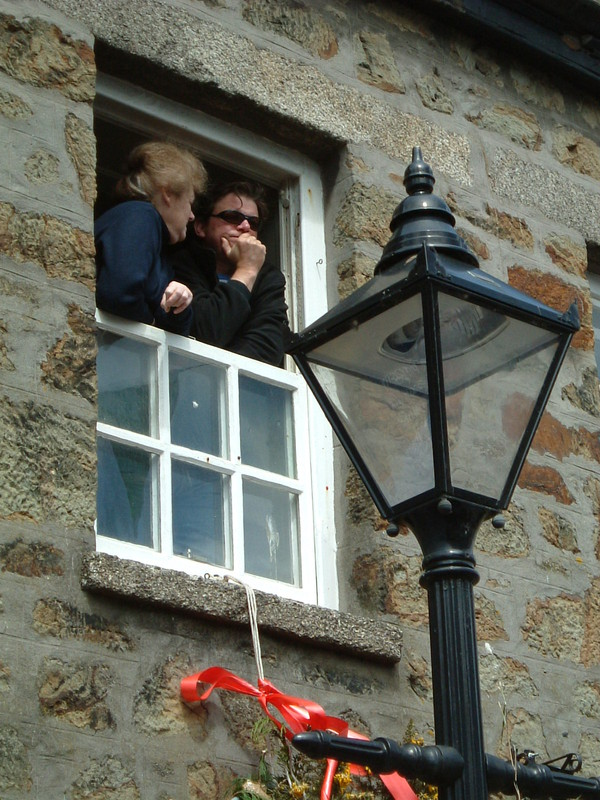 A couple peering from a window in Helston